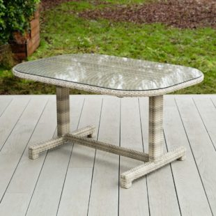 An oval outdoor dining table with a safety glass table top and cream grey weave rattan legs on a garden deck