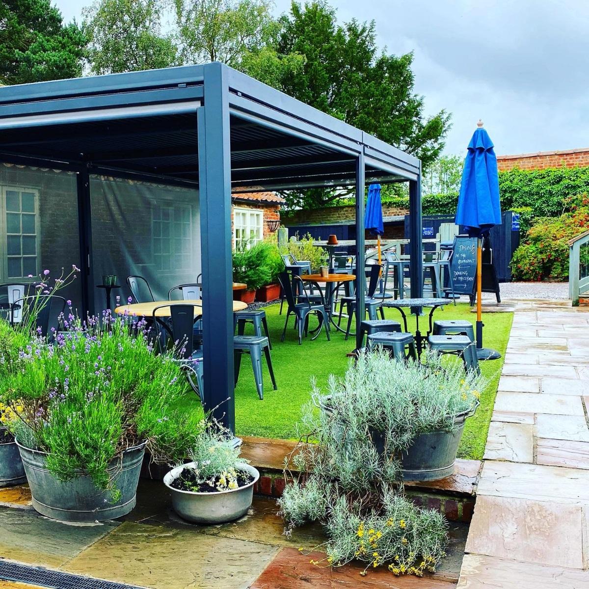 A rectangular grey metal gazebo covering 4 tables in a pub garden