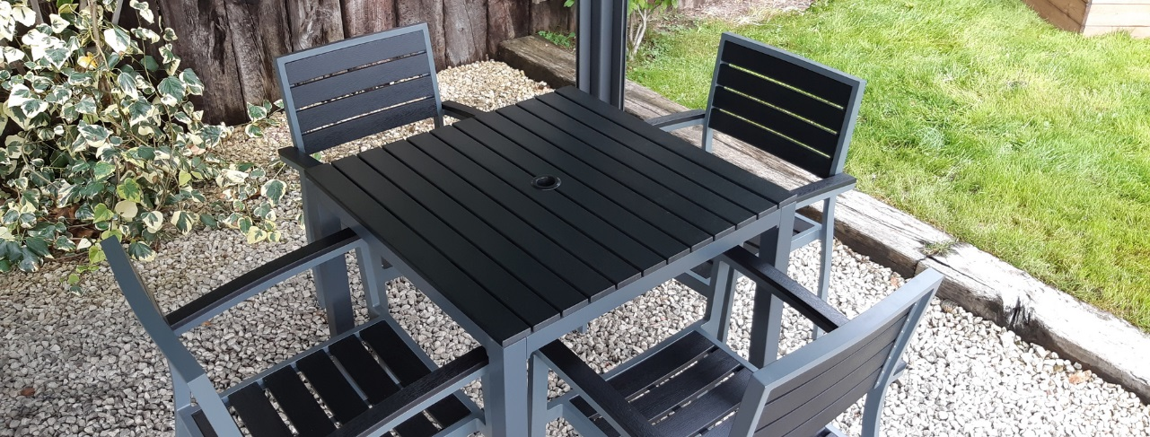 A square outdoor table and 4 chairs made from dark grey aluminium frame and black plastic slats for seat and table top on a gravel patio