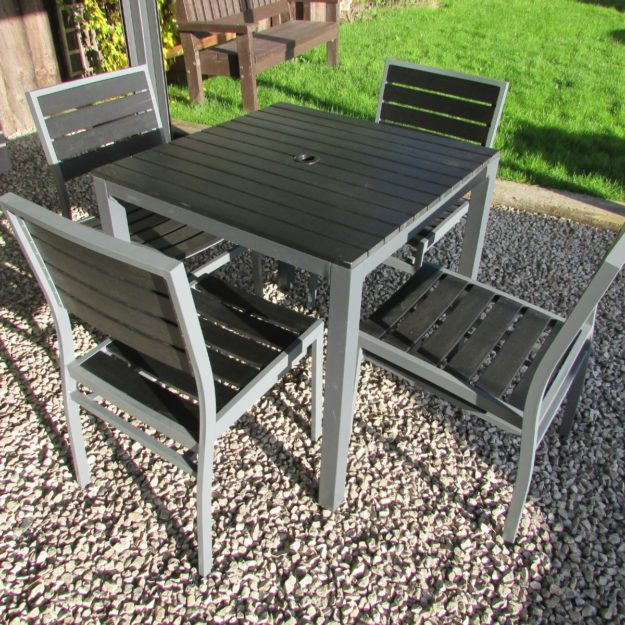 A square outdoor table with black plastic slats and a grey aluminium frame on a gravel patio with 4 matching diner chairs around it