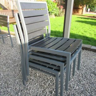 Black plastic slatted outdoor diner chair with grey aluminium frame in a stack of 3 chairs on a gravel patio