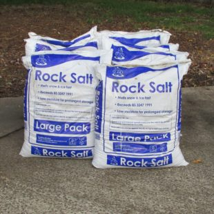 Six 25kg plastic bags of brown rock salt for deicing stacked in a pile on a concrete drive