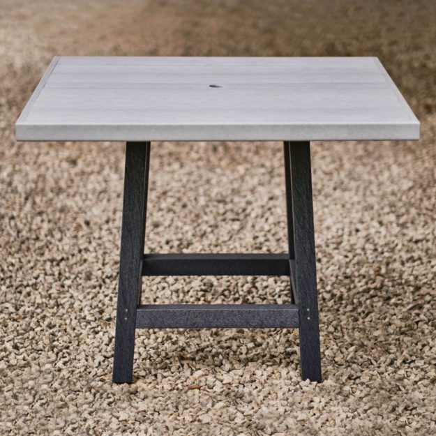 A square 2 tone grey outdoor dining table made from recycled plastic on a gravel patio