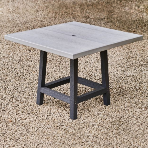 A square outdoor dining table made from recycled plastic with a light grey table top and 4 dark grey table legs on a gravel patio