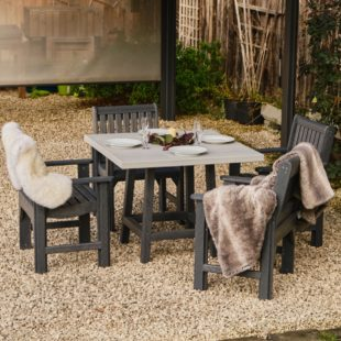 A square two tone grey recycled plastic outdoor table and 4 chairs set with cosy sheepskin rugs on a gravel patio