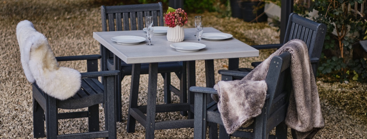 A square two tone grey recycled plastic outdoor dining table and 4 dark grey carver dining chairs with dinner settings and sheepskin blankets over the chairs on a gravel patio