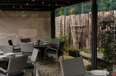 A close up of 3 round grey rattan tables and chairs sets underneath a grey metal gazebo with a flat roof on a gravel patio
