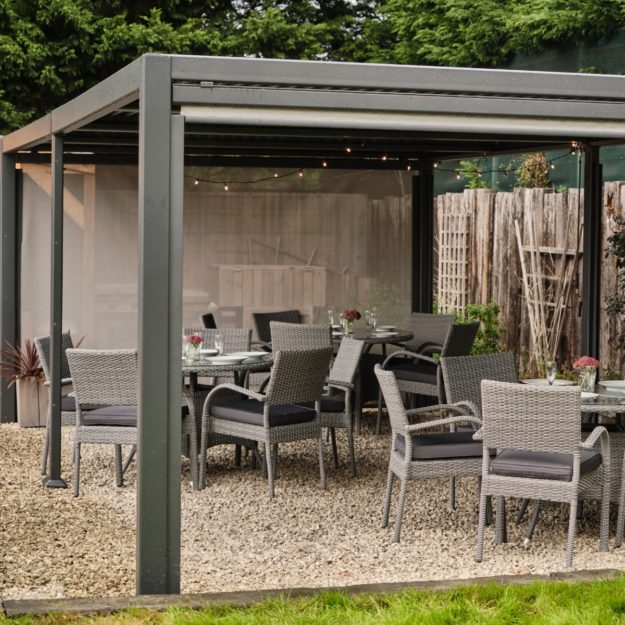 A dark grey rectangular metal gazebo with a waterproof flat roof with grey rattan round dining tables and matching chais underneath on a gravel patio