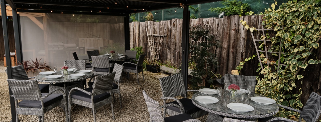 Three round grey rattan Stockholm range outdoor dining tables with 5 chairs around each table underneath a rectangular dark grey metal gazebo with a flat roof.