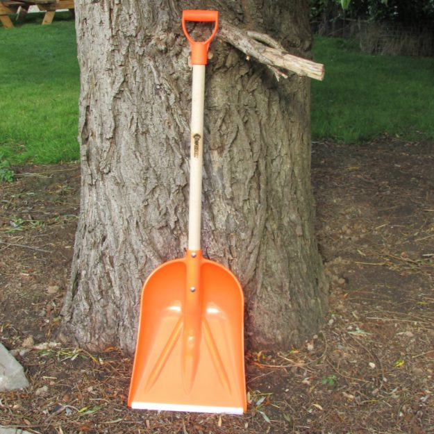 An orange wide bladed plastic snow shovel with a wooden pole and handle propped against a tree trunk