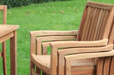 A stack of 3 teak outdoor chairs next to a square teak outdoor table on a patio