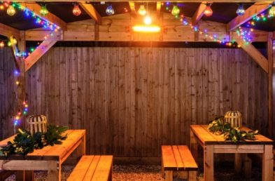A wooden gazebo with a pitched waterproof roof at night with coloured lights wrapped around it and 2 wooden rectangular tables and benches underneath
