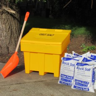 An orange snow shovel propped against a yellow grit bin with 6 bags of rock salt next to it