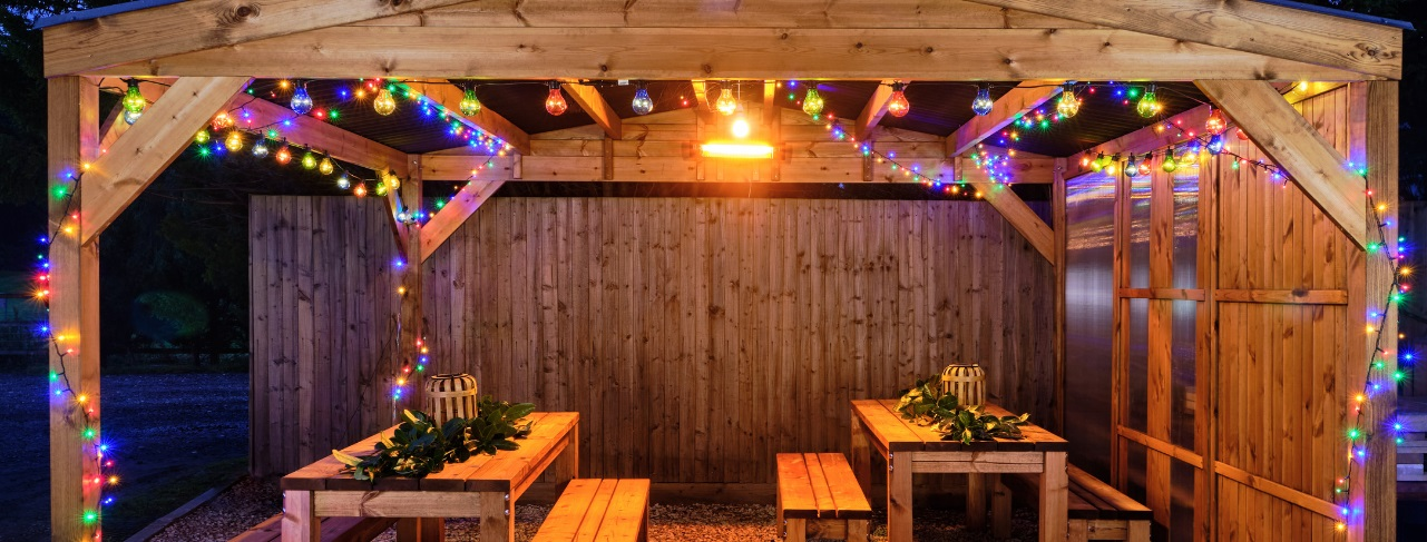 A wooden gazebo with a waterproof apex roof decorated with lit up multi coloured christmas lights with 2 rectangular wooden tables and 4 benches underneath the tables are decorated for christmas