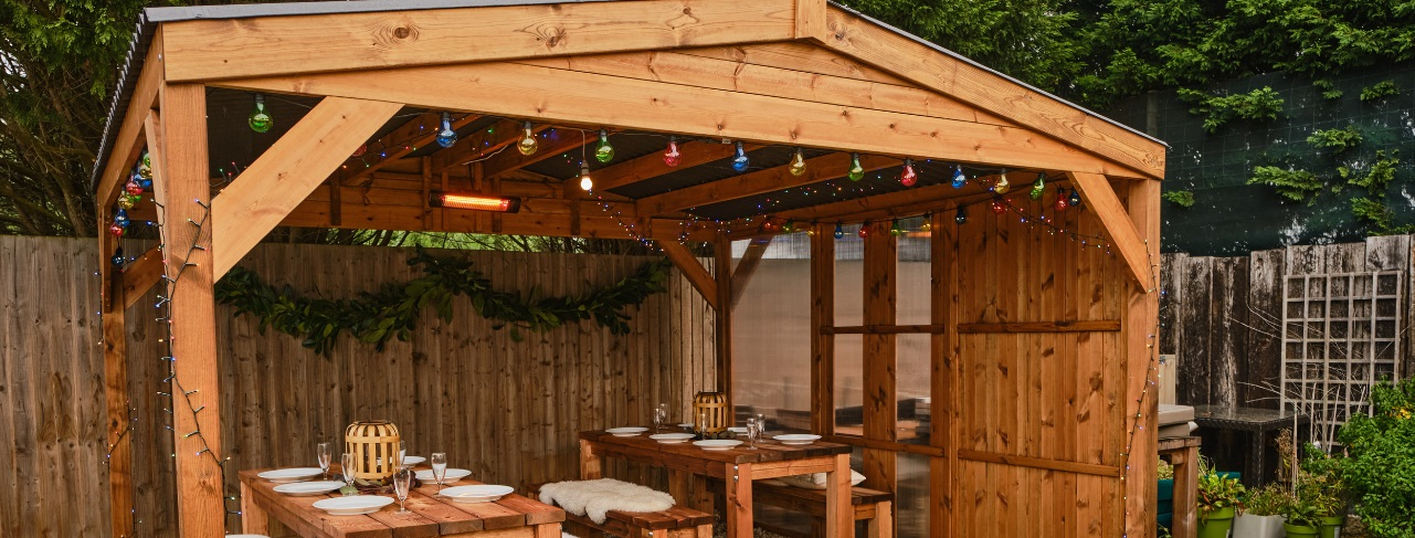 A wooden gazebo with a waterproof roof with christmas lights and 2 tables of 6 set for christmas dinner