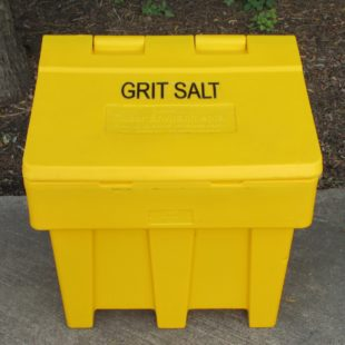 A bright yellow rectangular plastic grit bin on a concrete drive way