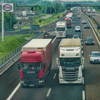 A motorway with 2 lorries side by side making deliveries