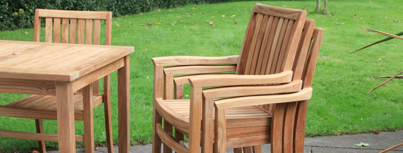 A stack of 3 outdoor teak dining armchairs and a square table on a patio