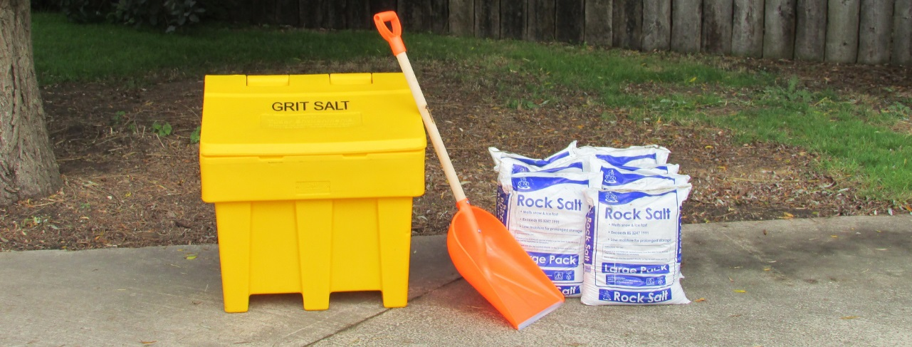 A yellow plastic grit bin with a plastic orange shovel and 6 bags of rock salt in a pile next to it