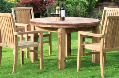 A round wooden table on a lawn with 4 teak stacking armchairs around it