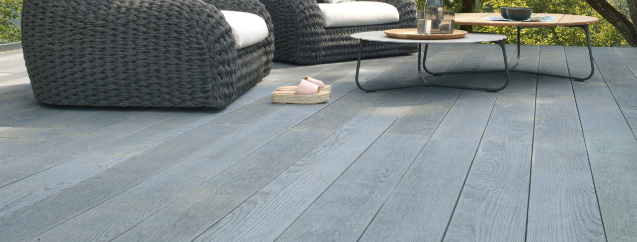 A dark grey wood effect deck made from Millboard Brushed Basalt deck planks with 2 outdoor armchairs and 2 coffee tables