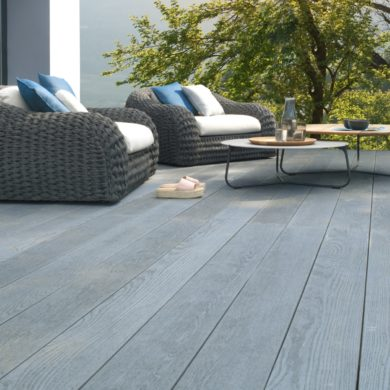 A dark grey poly resin garden Millboard deck with 2 large armchairs on and 2 small coffee tables