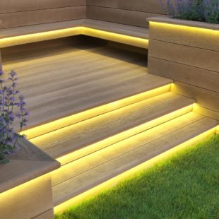A golden oak coloured wood effect set of garden decking steps with lights under the treads illuminating the steps