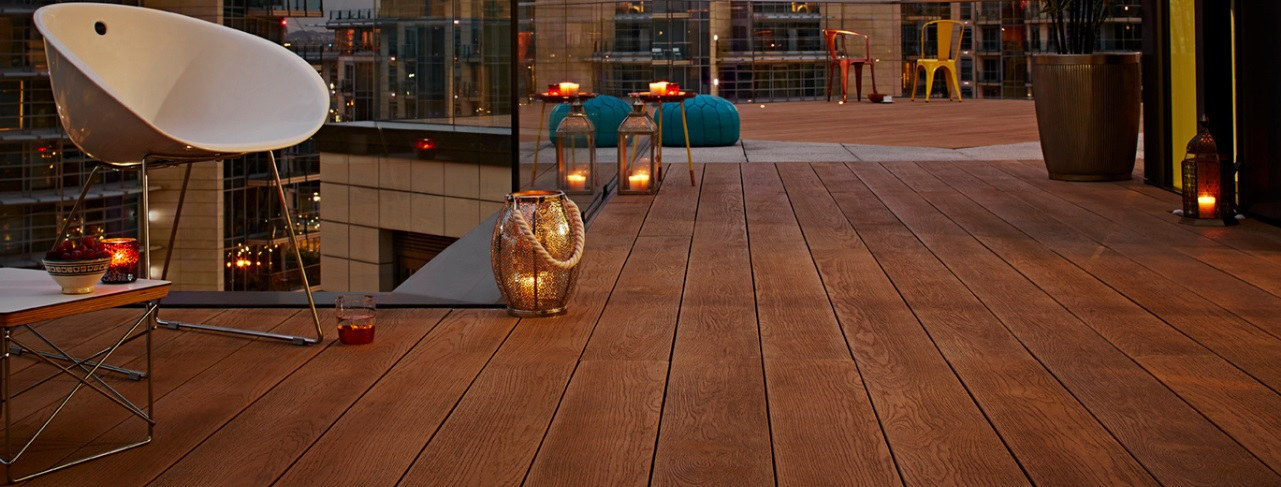 A copper coloured wood effect deck with outdoor chairs and floor lanterns with lit candles