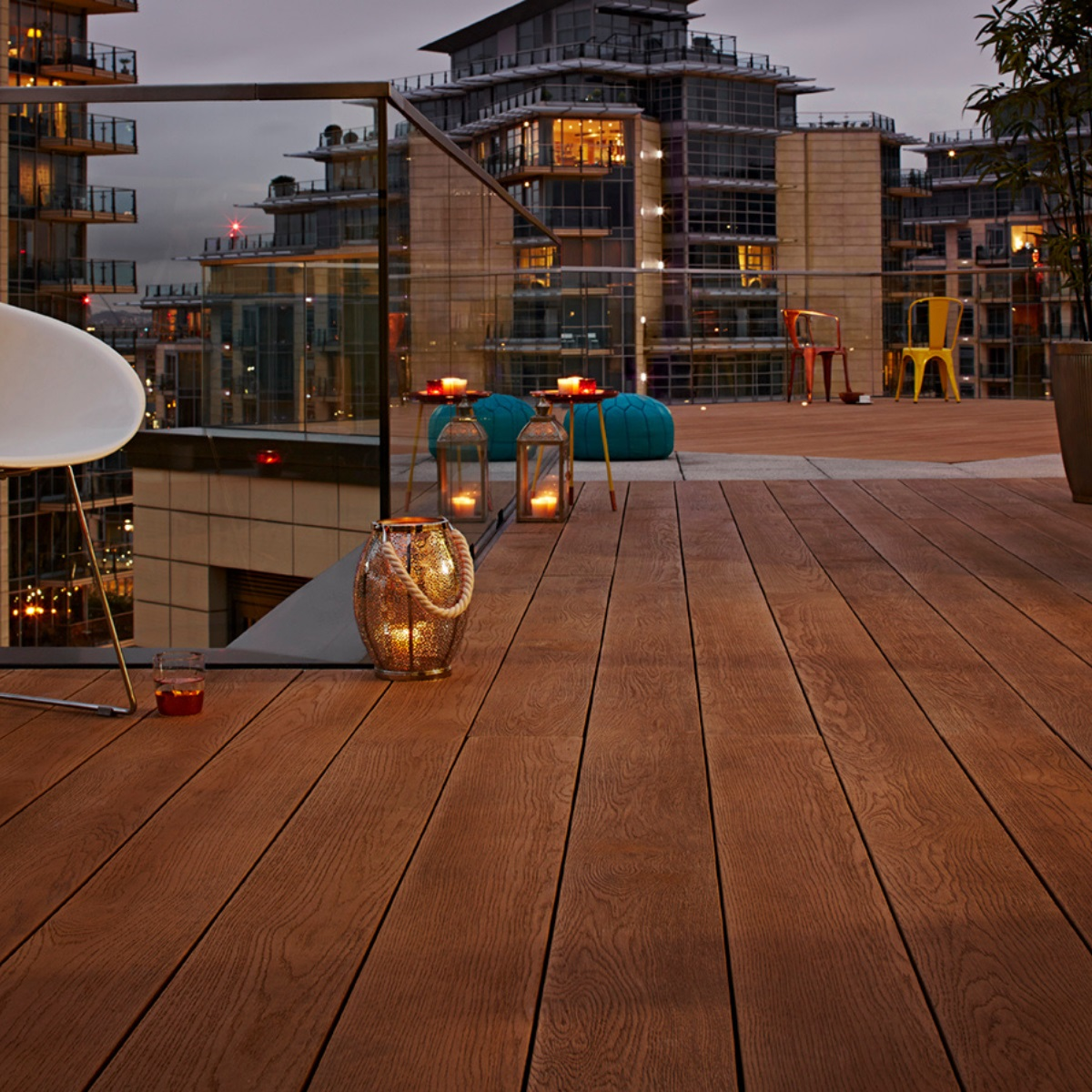 A copper coloured wood effect garden deck on a rooftop terrace with outdoor chairs on top