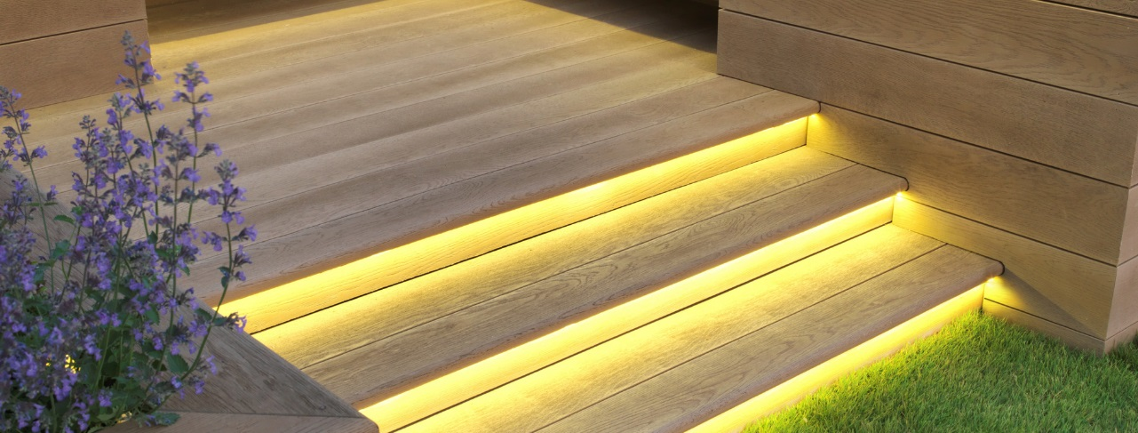 A light golden coloured millboard deck set of steps going from deck to grass
