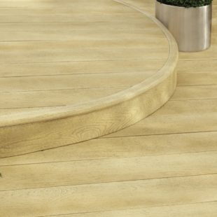 A curved step on a garden deck showing a close up of the edge of the step which is a rounded edge