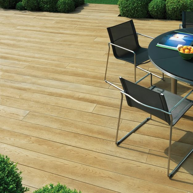 A golden colour wood effect garden deck made from Millboard decking with a dark grey garden dining table and chairs set on top