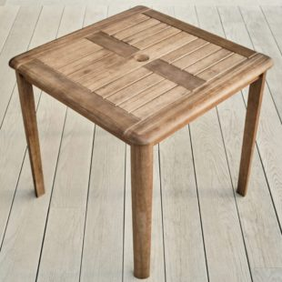 A square hard wood outdoor table with a parasol hole in middle of the table on a garden deck