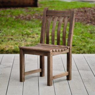 A hard wood outdoor dining chair with slatted back and seat on a garden deck