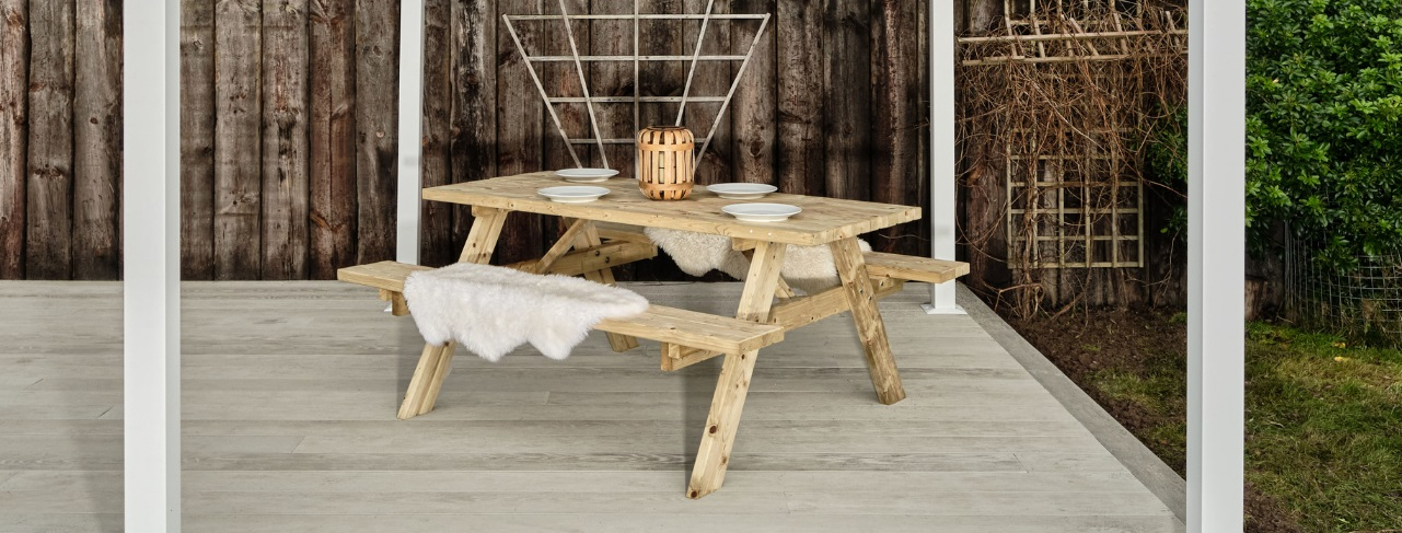 A wooden 8 seater picnic table on a grey garden deck with place settings