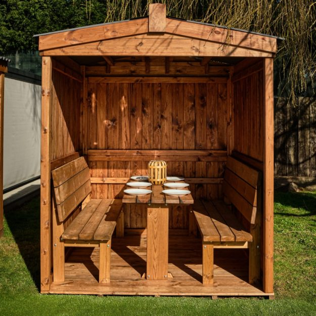 A robust wooden outdoor dining cabin with 3 enclosed sides and a weather proof roof inside 2 benches and a table for 6 people