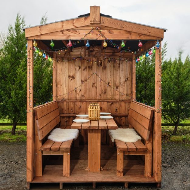 A wooden outdoor dining cabin with a waterproof roof and fixed table and benches inside seating up to 6 people