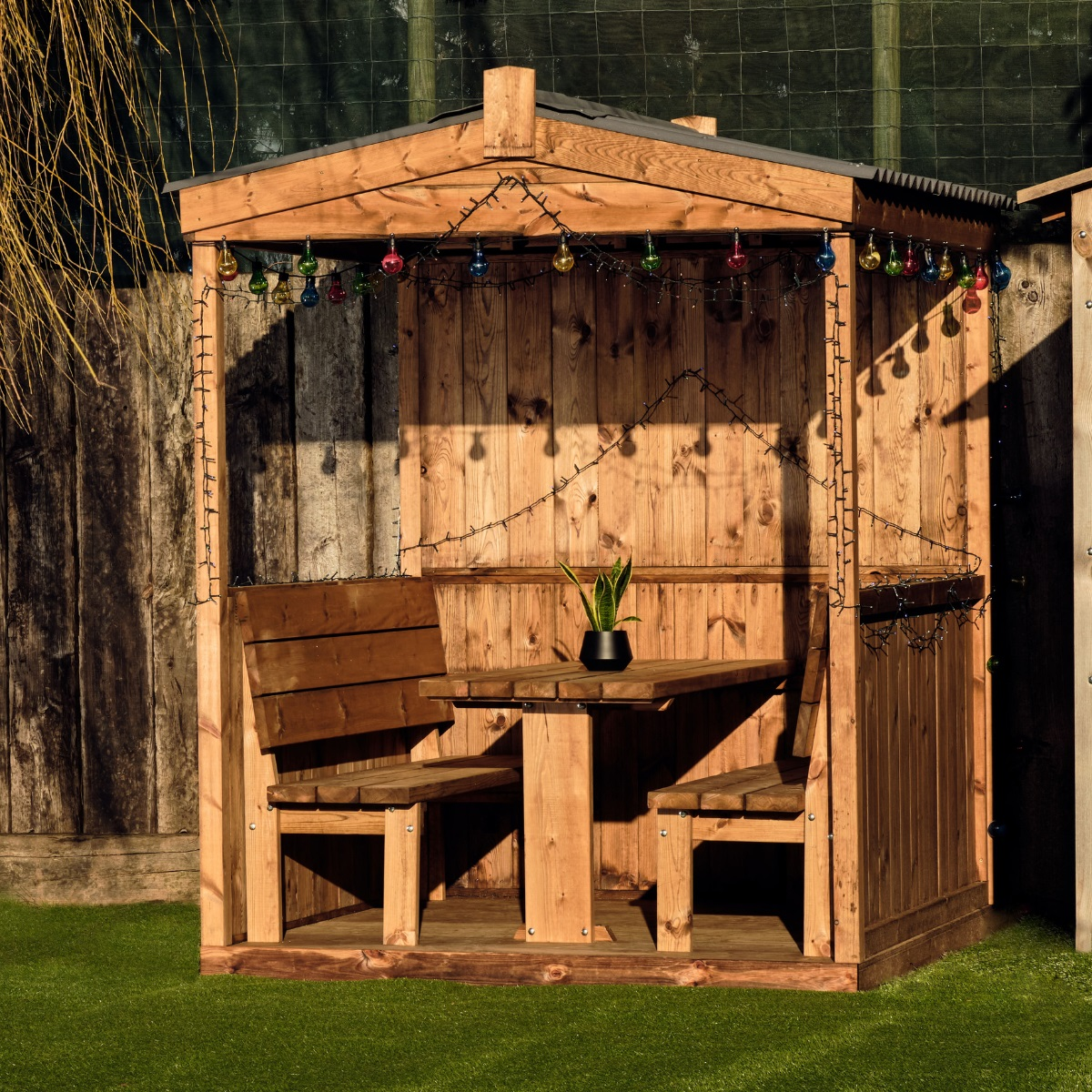 A wooden outdoor dining cabin with roof and back but with open half sides and an open frontage. Bench seats and table for 6 people are fixed inside