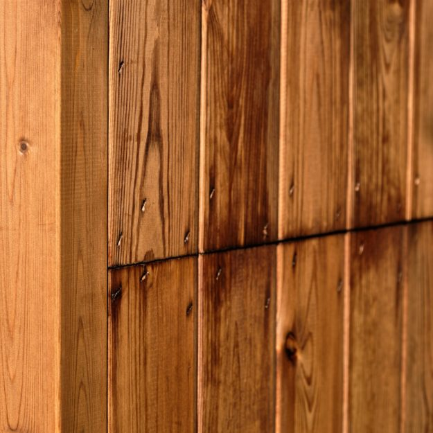 A wooden wall side panel of an outdoor dining cabin