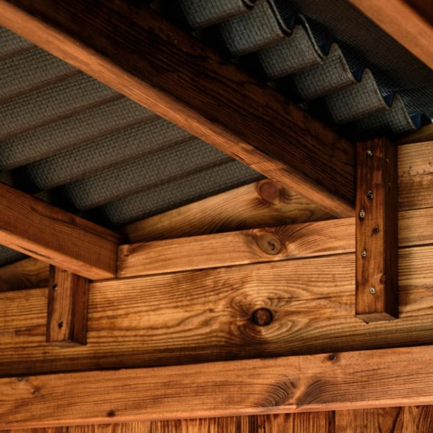 Showing the underside of an apex corrugated bitumen roof of a wooden outdoor dining cabin with wooden beams