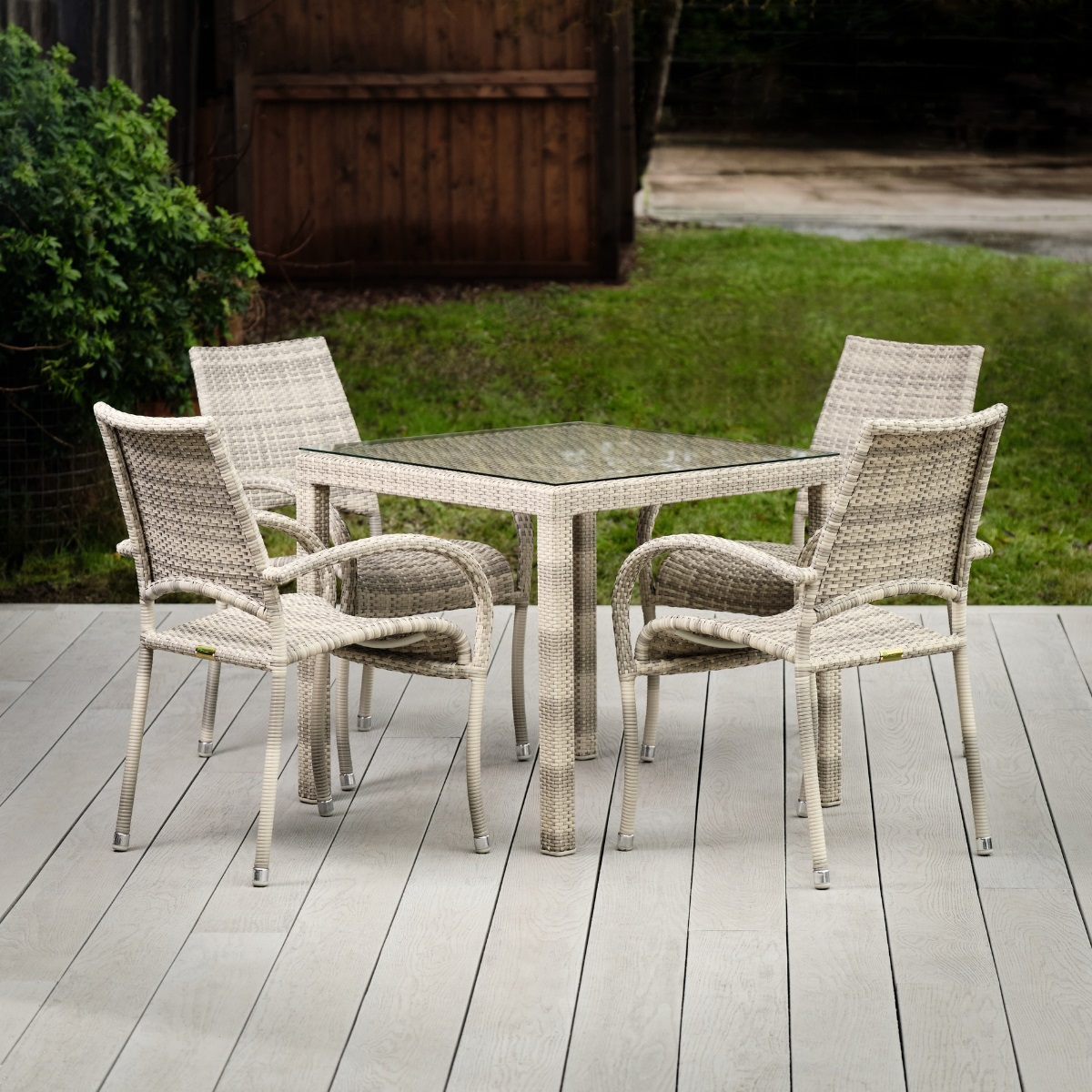A cream and grey rattan outdoor square dining table and 4 matching chairs on a light grey deck