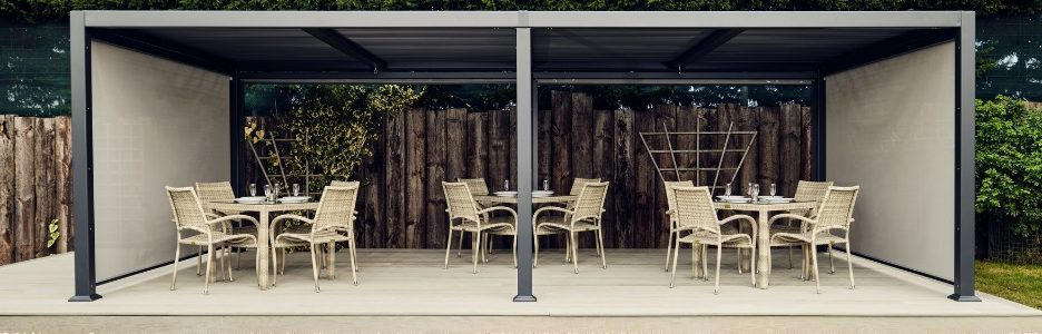 A dark grey metal rectangular gazebo with a flat slatted waterproof roof on a light grey deck with grey rattan tables and chairs arranged on it