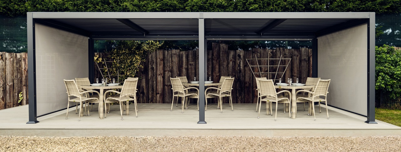 A 7 metre long dark grey metal gazebo with slatted roof on a grey deck with 3 tables underneath