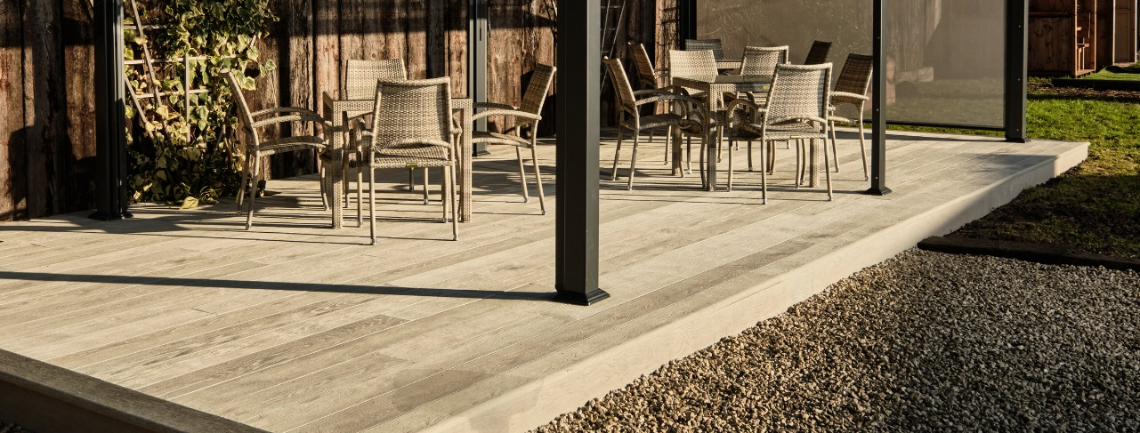 A light grey millboard deck 9m long by 4m wide with grey rattan tables and chairs and a dark grey metal gazebo on top