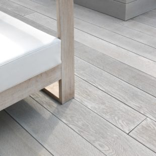 A light grey wood effect millboard deck in a garden with outdoor armchairs on top