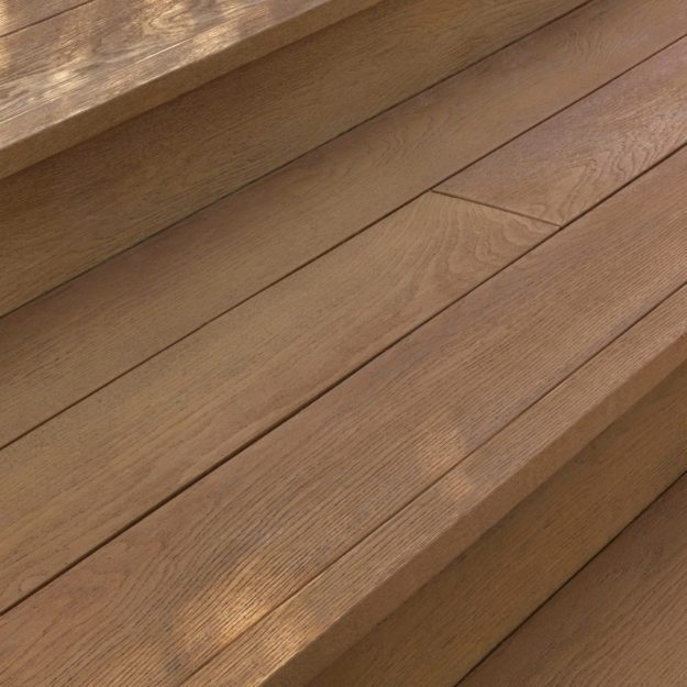 A close up of square edging on a copper coloured wood effect garden deck