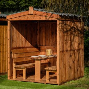 A 3 sided wooden dining cabin with a weather proof apex roof and fixed table and benches inside on grass