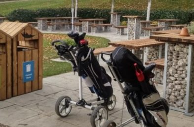 A golf club patio with 2 golf bags on trolleys in the foreground, in the background poseur height wooden topped tables with rock filled cages for table pedestal legs and a wooden litter bin to the side