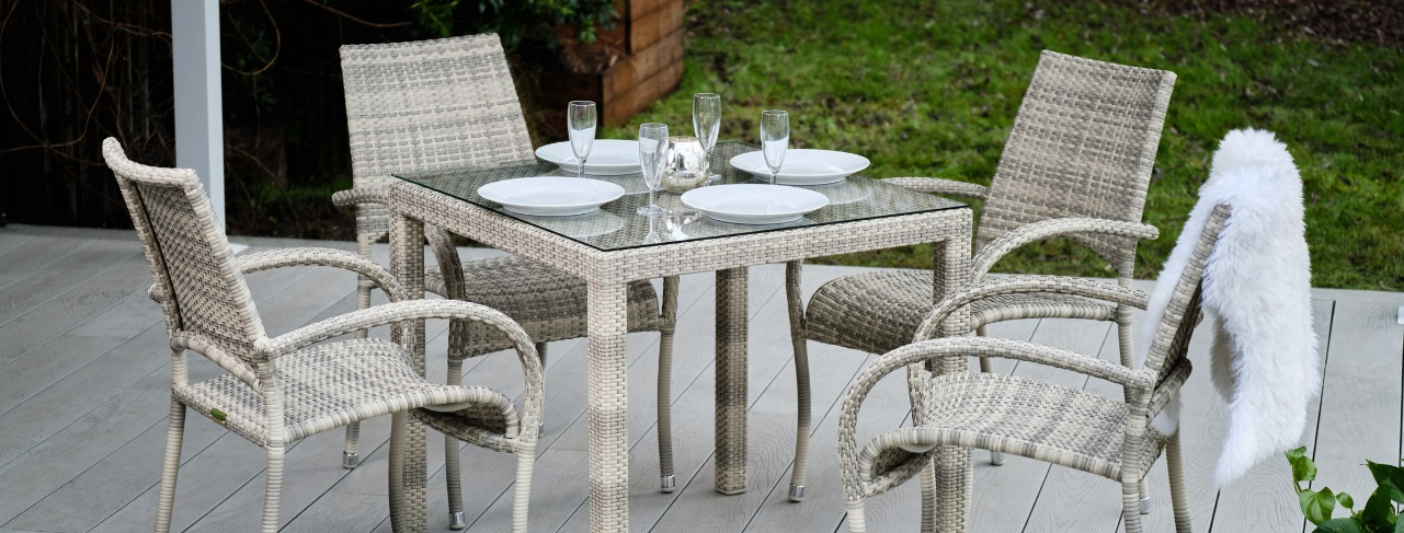 A cream grey rattan outdoor square dining table and chairs set on a deck