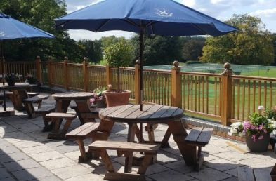 4 circular wooden picnic tables with blue parasols on a terrace